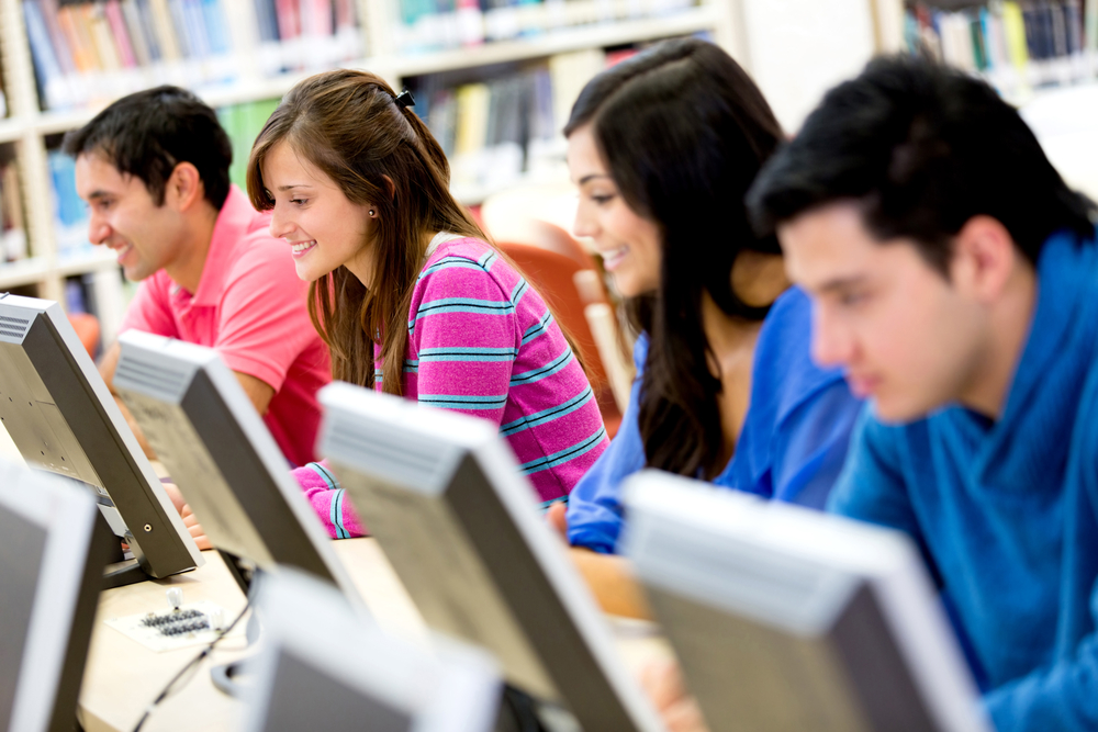 Group of young people studying at the library using computers