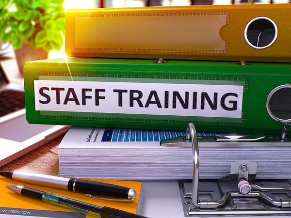Staff Training - Green Office Folder on Background of Working Table with Stationery and Laptop. Staff Training Business Concept on Blurred Background. Staff Training Toned Image. 3D.